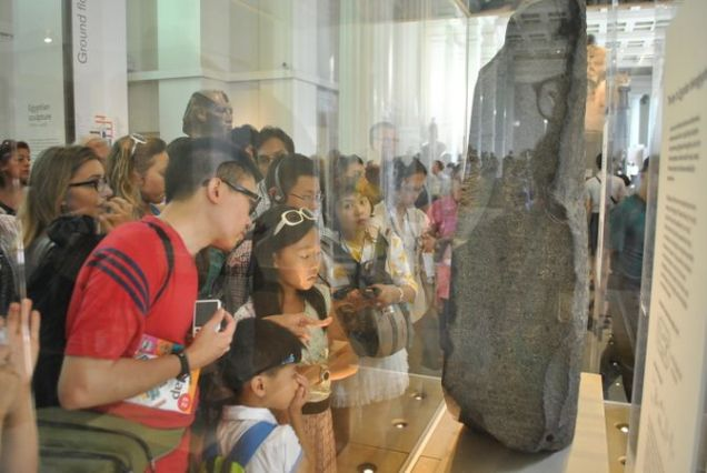 671px-Tourist_watching_Rosetta_Stone_at_British_Museum