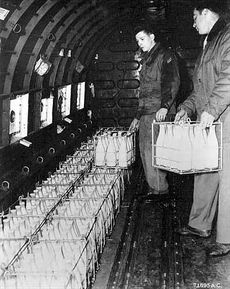 Soldiers loading milk onto a plane