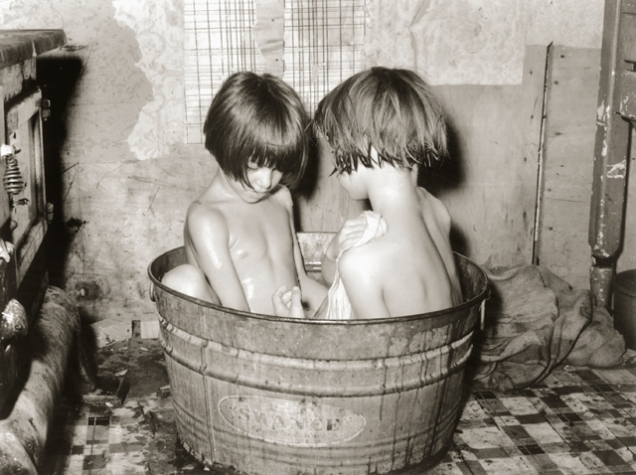 picture of two children bathing in a small metal tub